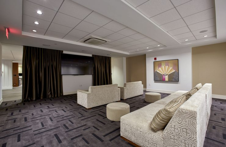 media room with comfy sofas, tables and large flat screen TV