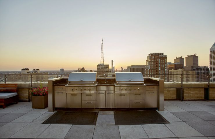 stainless steel gas grills on sky deck with sunset view of the city