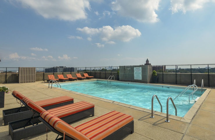 large rooftop pool with padded lounge chairs