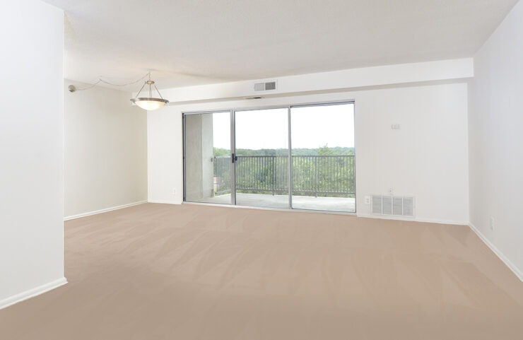 large carpeted living and dining area with access to balcony