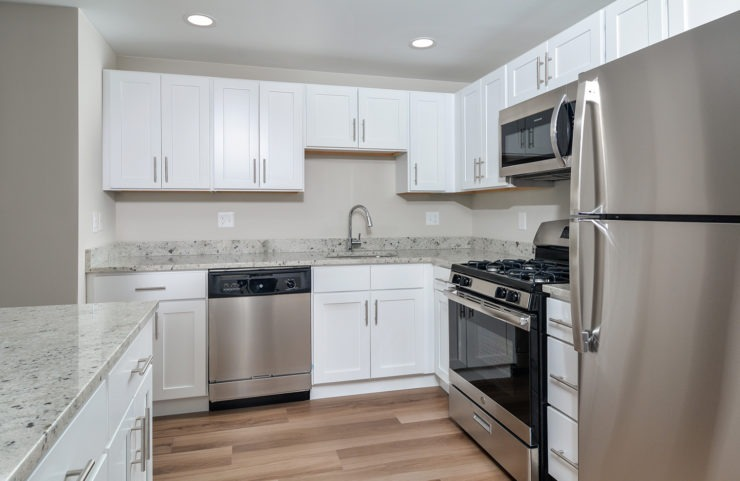 Penthouse kitchen with white cabinets and stainless steel appliances