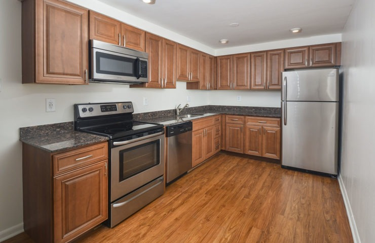 kitchen with medium tone wood cabinets, SS appliances and hardwood floors