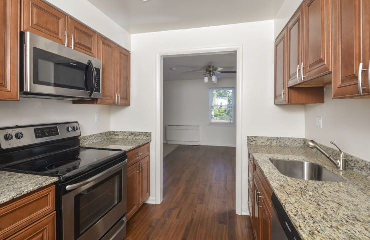 Galley Style Kitchen with hardwood floors looking out into dining room