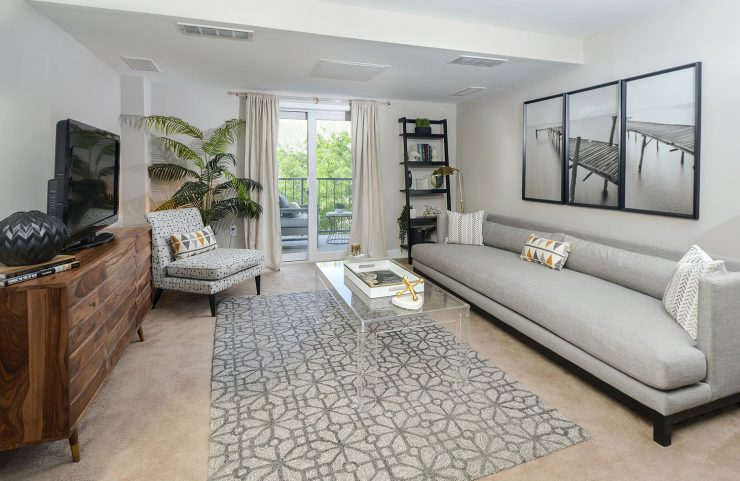 large living room with wall to wall carpet and sliding door out to private balcony