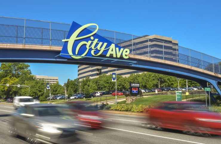 photo of cars driving under the City Ave sign on bridge