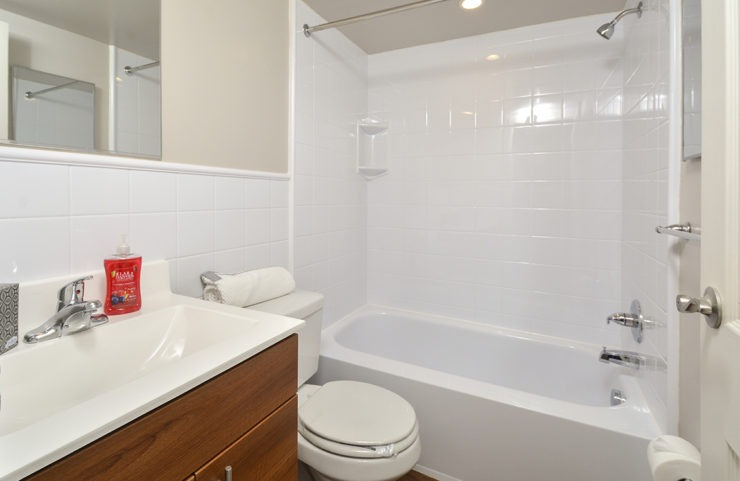 bathroom with white tile and cultured marble sink