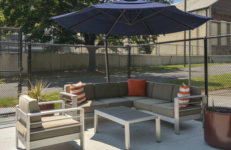 comfy seating area with blue umbrella for shade