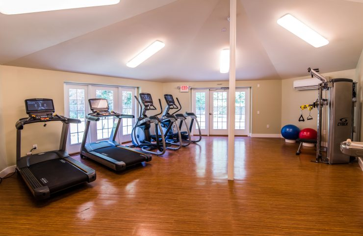 fitness center with treadmills and elliptical machines