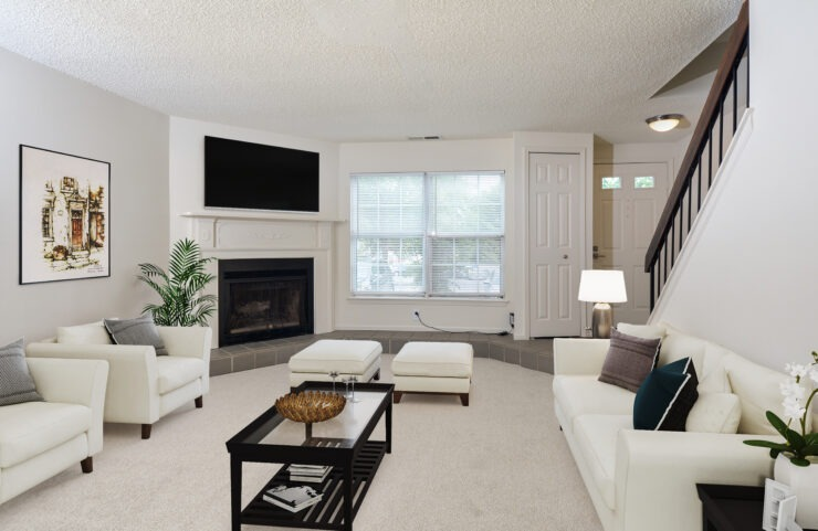 carpeted living room with a wood burning fireplace