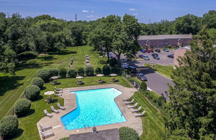 aerial view of outdoor pool with apartment in background