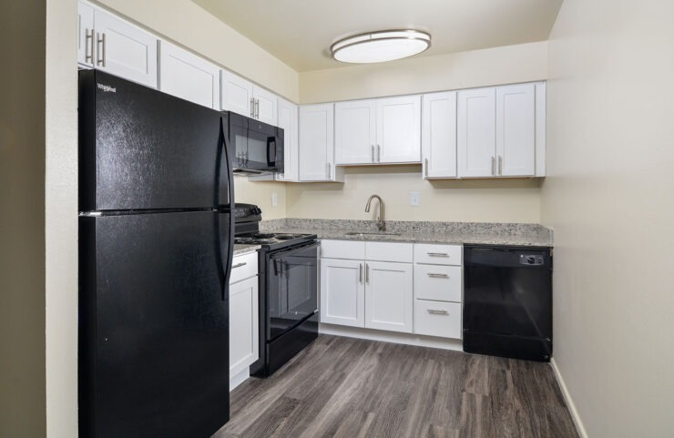 upgraded kitchen with white cabinets and black appliances