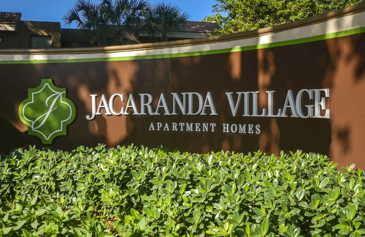 Jacaranda Village Apartments curved sign at entrance