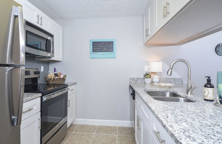updated kitchen with white cabinets and stainless steel appliances
