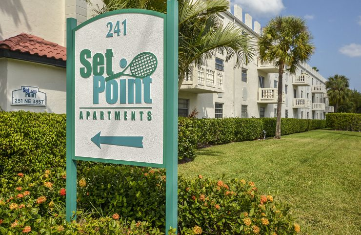set point signage with apartments in the background