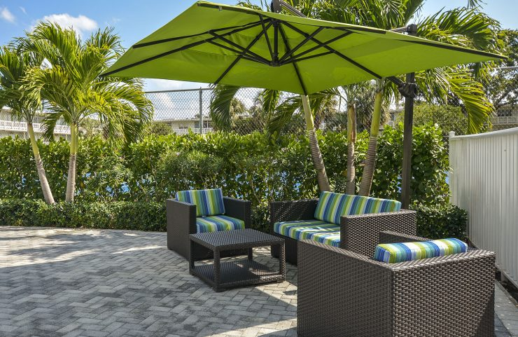 comfy seating area by pool with large umbrella for shade