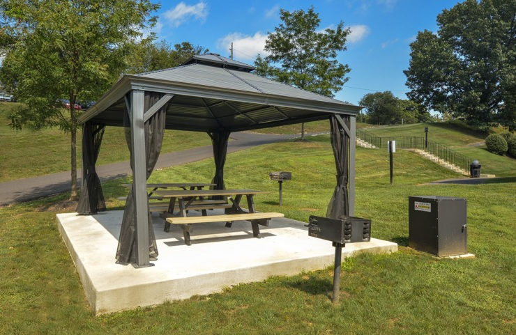 picnic bench under tent with grills