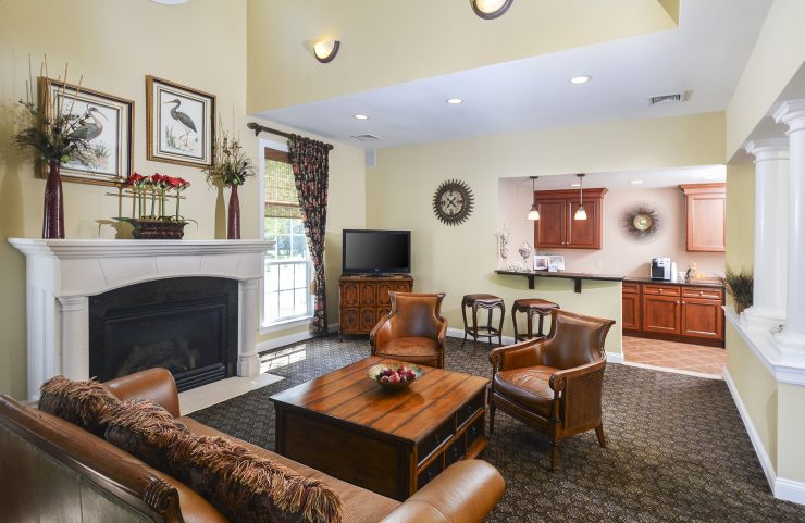clubhouse with cozy sofa and chairs next to a fireplace
