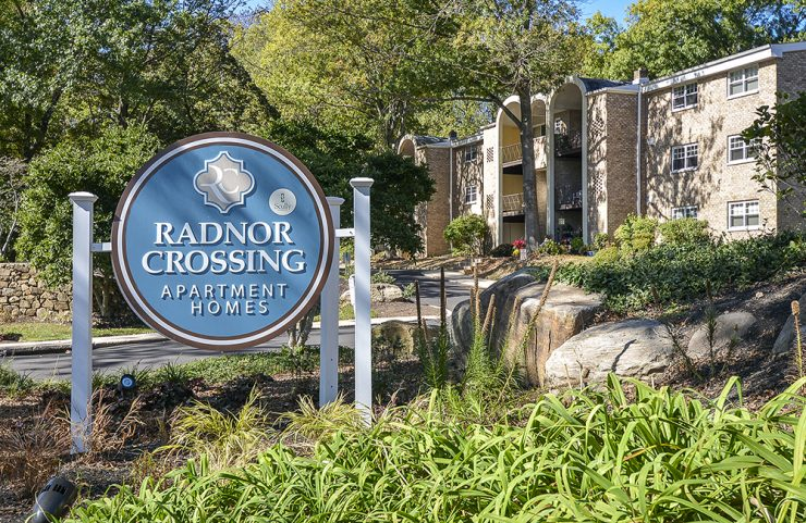 round blue radnor crossing sign at entrance of community