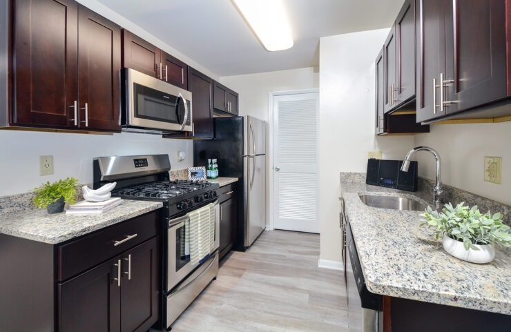 Galley style kitchen with stainless steel appliances and granite countertops