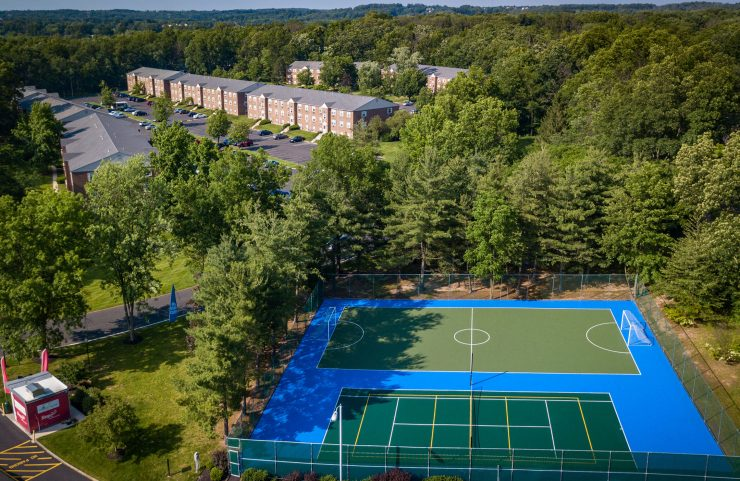 aerial view of sports court, lush trees and apartments