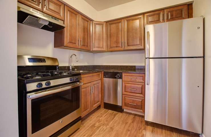 updated kitchen with medium wood cabinets and gas stove