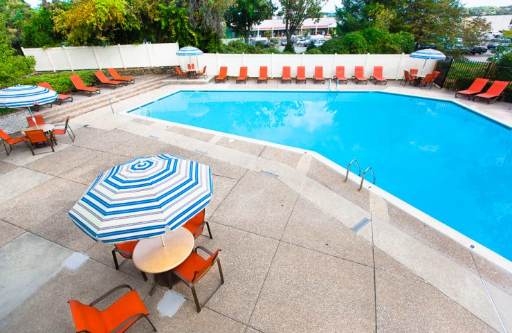 large outdoor pool with plenty of lounge chairs