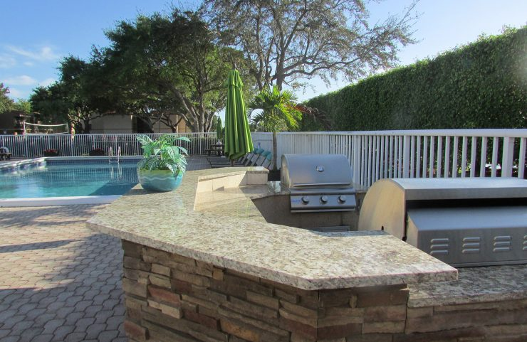 outdoor kitchen area with gas grills by the pool