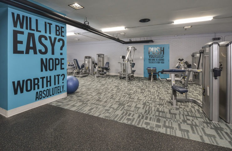 strength training equipment with motivational quotes on wall