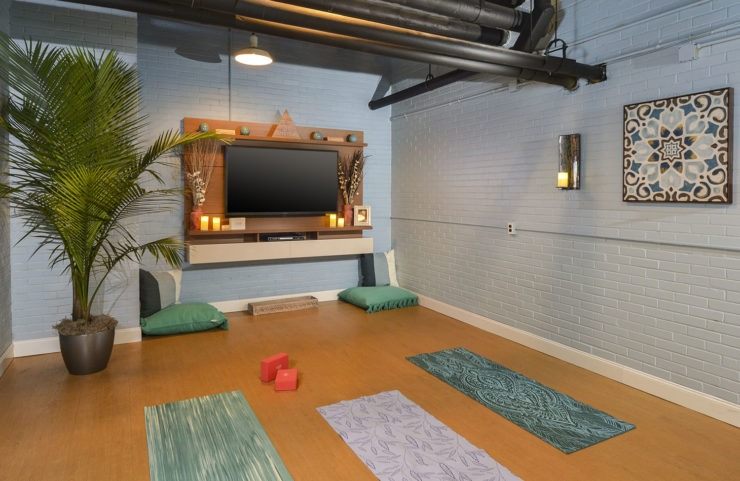 yoga room with tv, pillows and mats