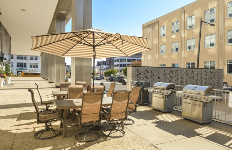 patio with umbrella tables and gas grills