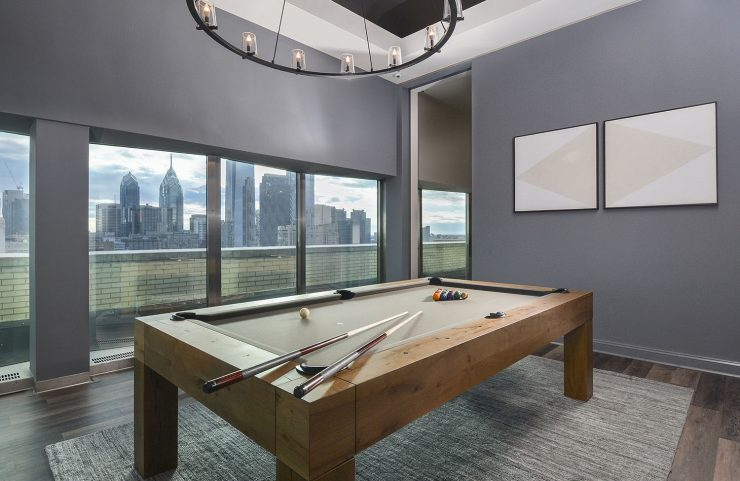 billiards table surrounded by large windows with a view of center city
