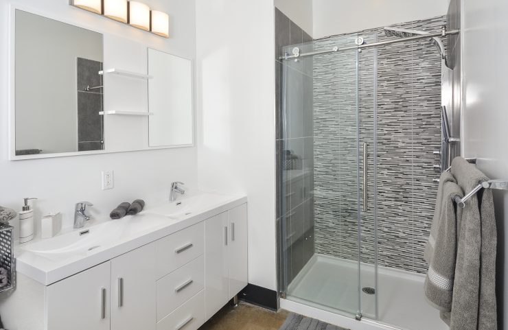 Modern bathroom with double sink and tiled shower