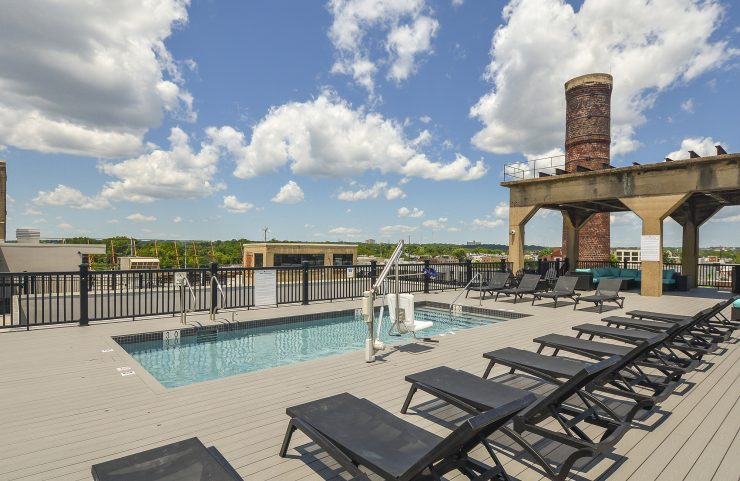 rooftop pool with an array of lounge chairs surrounding the pool
