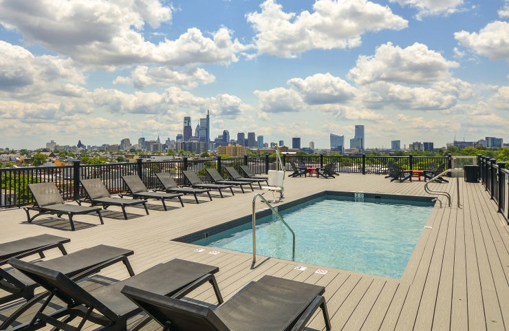 rooftop pool with lounge chairs and views of the city