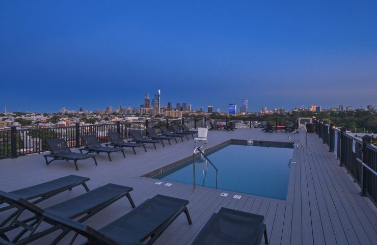 looking out at the twinkling lights of the city from the rooftop deck