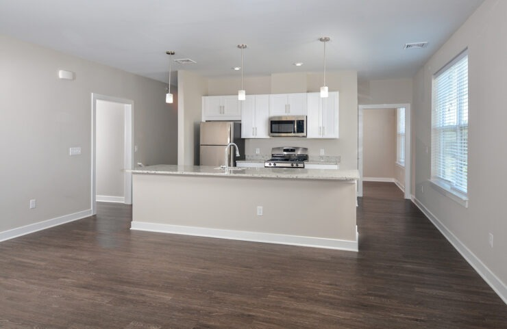 Open floorplan kitchen and living room with plank flooring and kitchen island