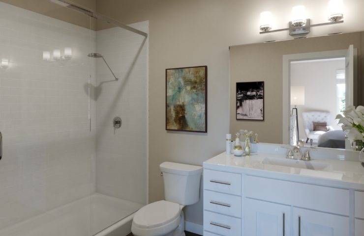 bathroom with tile shower and white vanity