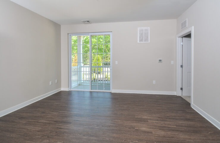 living room with plank flooring and sliding doors leading out to the balcony