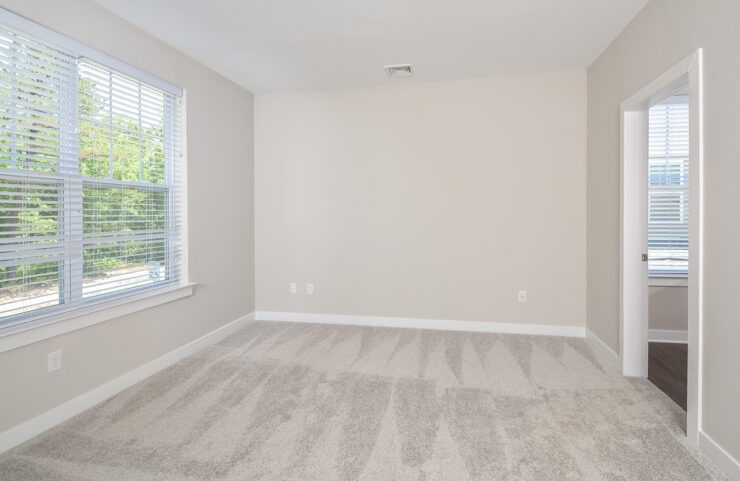 bedroom with large window and neutral color carpet