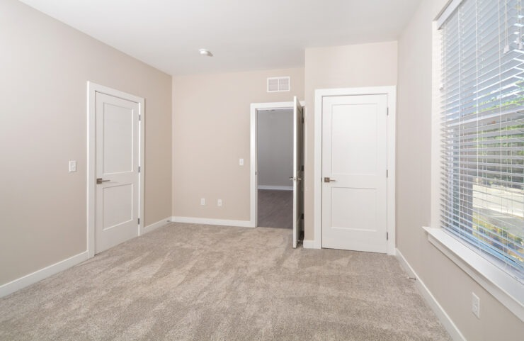 master bedroom with carpet and large closet space