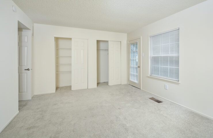carpeted bedroom with double closets