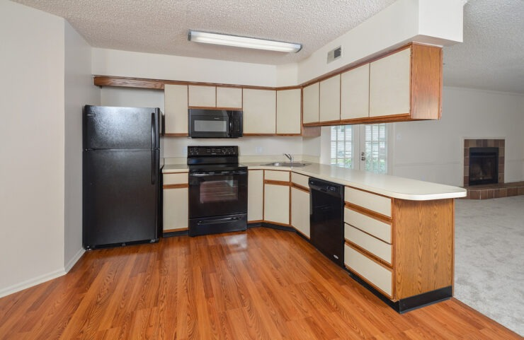standard kitchen with black appliances and plank flooring