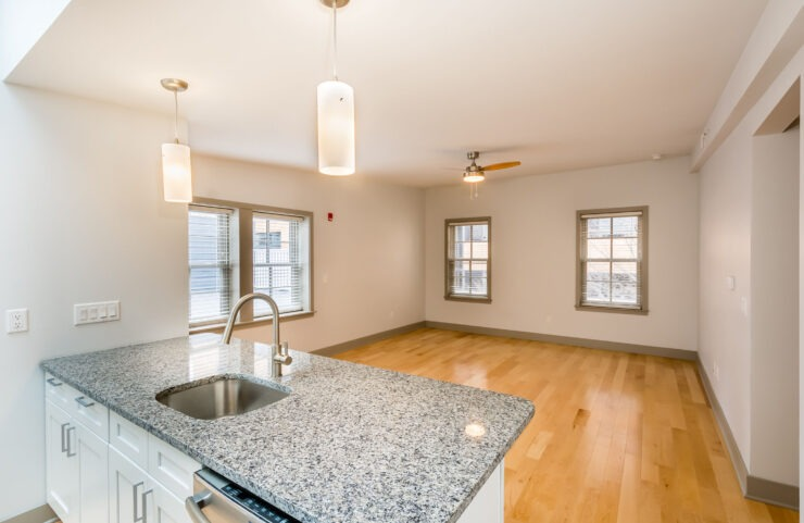 Granite Kitchen Island, Decorative Overhead Light Fixtures and Ceiling Fan In Open Layout